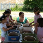 Volunteer Rebecca Guest leads camp participants in washing artifacts on site